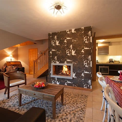 An spacious open plan living/dining area with an open log fire