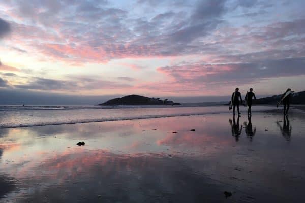 Surfers leaving Bantham Surf at dusk